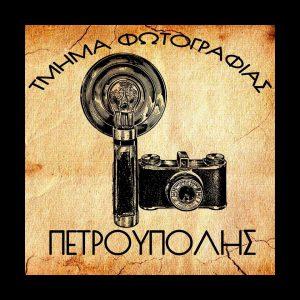 """Απεικόνιση μίας φωτογραφικής μηχανής με λογότυπο """"τμήμα φωτογραφίας Πετρούπολης""""."""